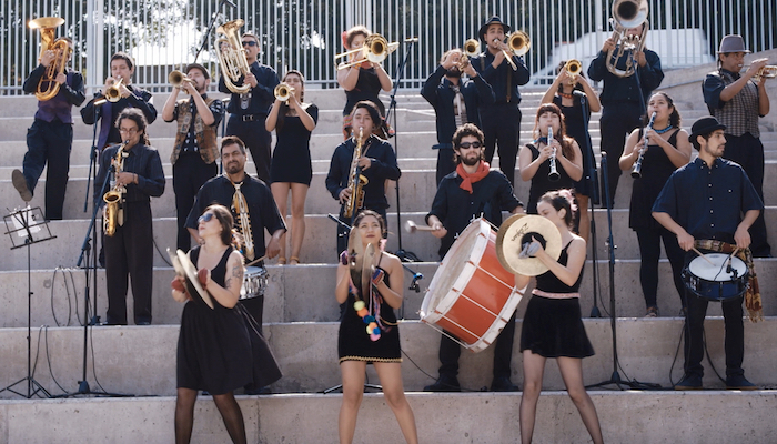 A small marching band performs on an outdoor stairway in a scene from the documentary Santiago, Italia
