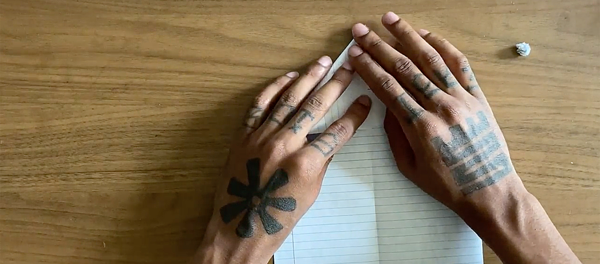 The tattooed hands of African American artist Hakim Callwood begin to fold a piece of lined paper on a wooden surface into a paper airplane