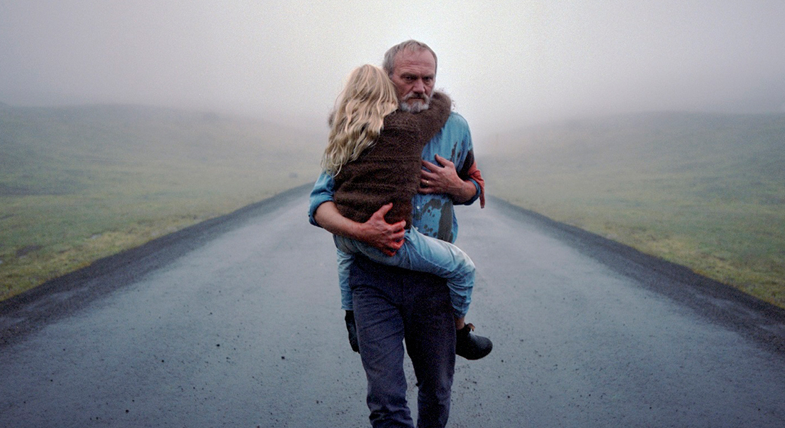 a grieving man (Ingvar Sigurðsson) carries his daughter on his waist along a foggy road