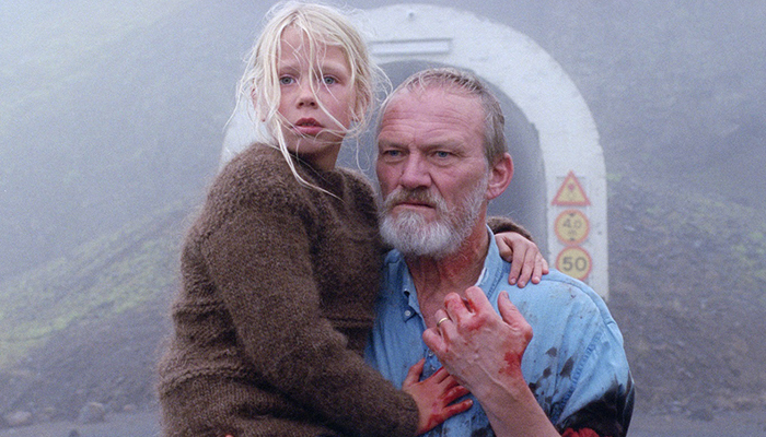 a grieving man (Ingvar Sigurðsson) carries his daughter on his waist in front of tunnel entrance