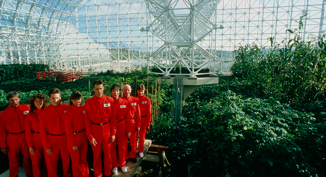 eight men and women in red uniforms in the greenhouse like structures of Biosphere 2