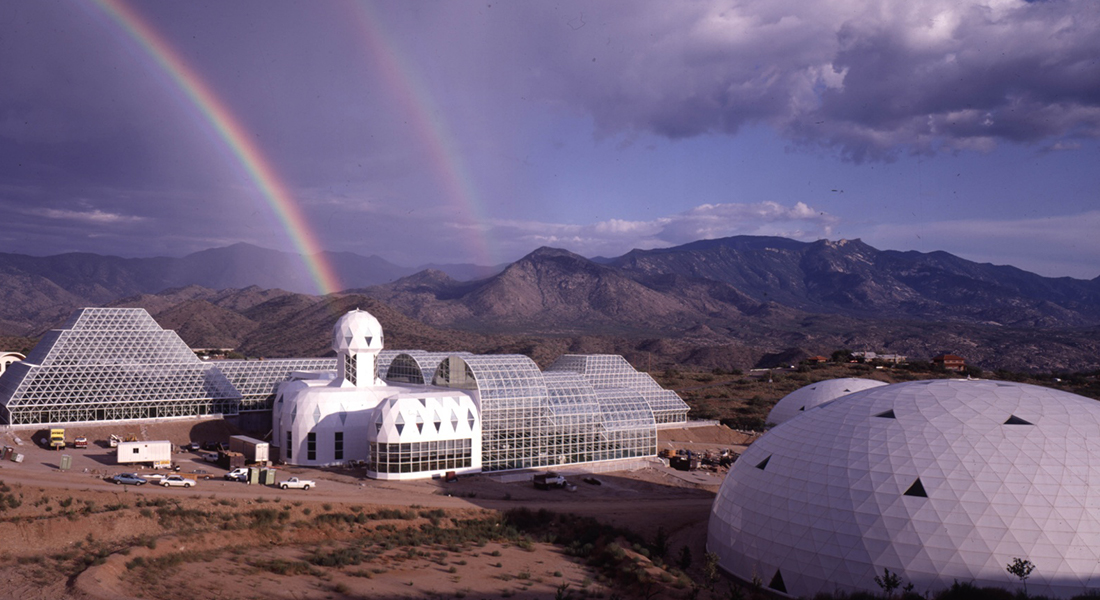 the metal and glass structures of Biosphere 2 set against mountains and a double rainbow