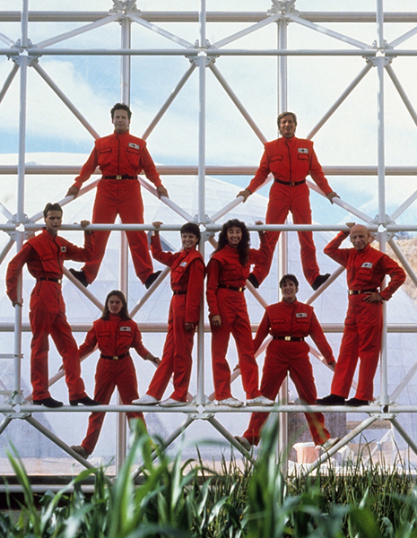 eight men and women in red uniforms standing on metal scaffolding