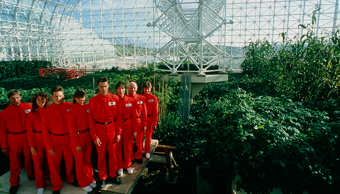 eight men and women in red uniforms in a metal and glass green house