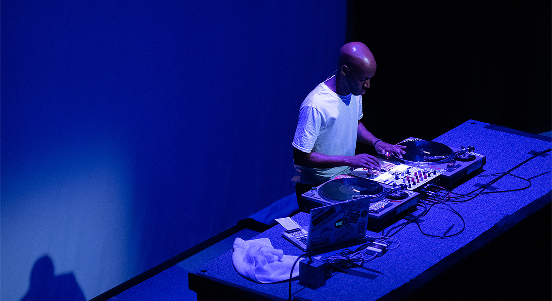 DJ Krate Digga on blue-lit stage with his decks