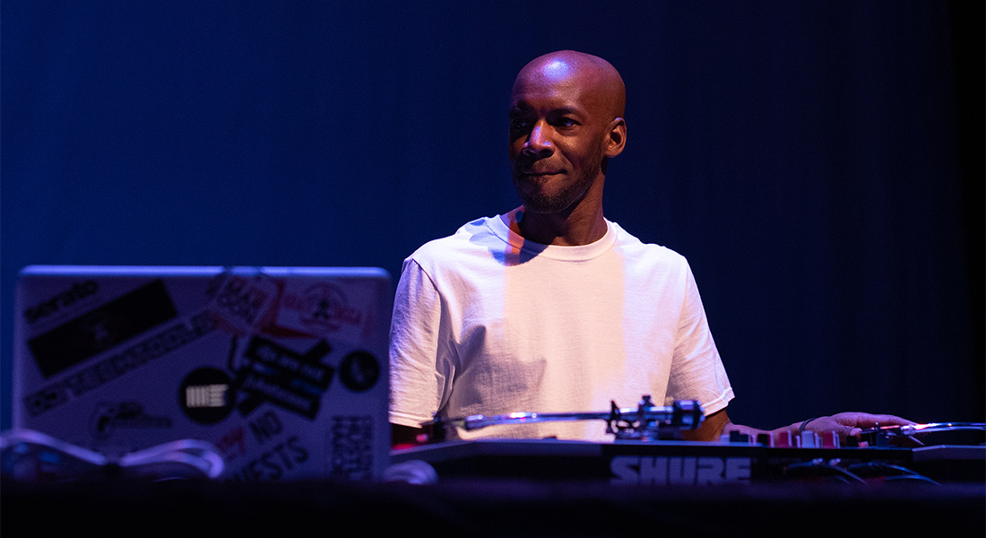 DJ Krate Digga in white tee-shirt on a blue-lit stage