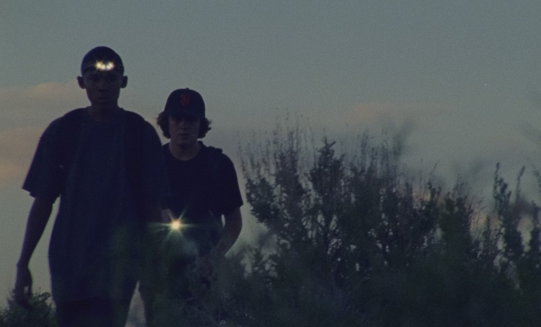 Two teenage boys with flashlights walk toward the camera in a scene from Stanya Kahn's short film No Go Backs