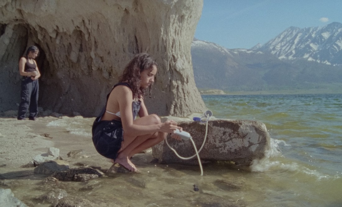 A teenage girl crouches by the shore, pumping sea water through a filter pump as another girls stands in the distance behind her in a scene from Stanya Kahn's No Go Backs