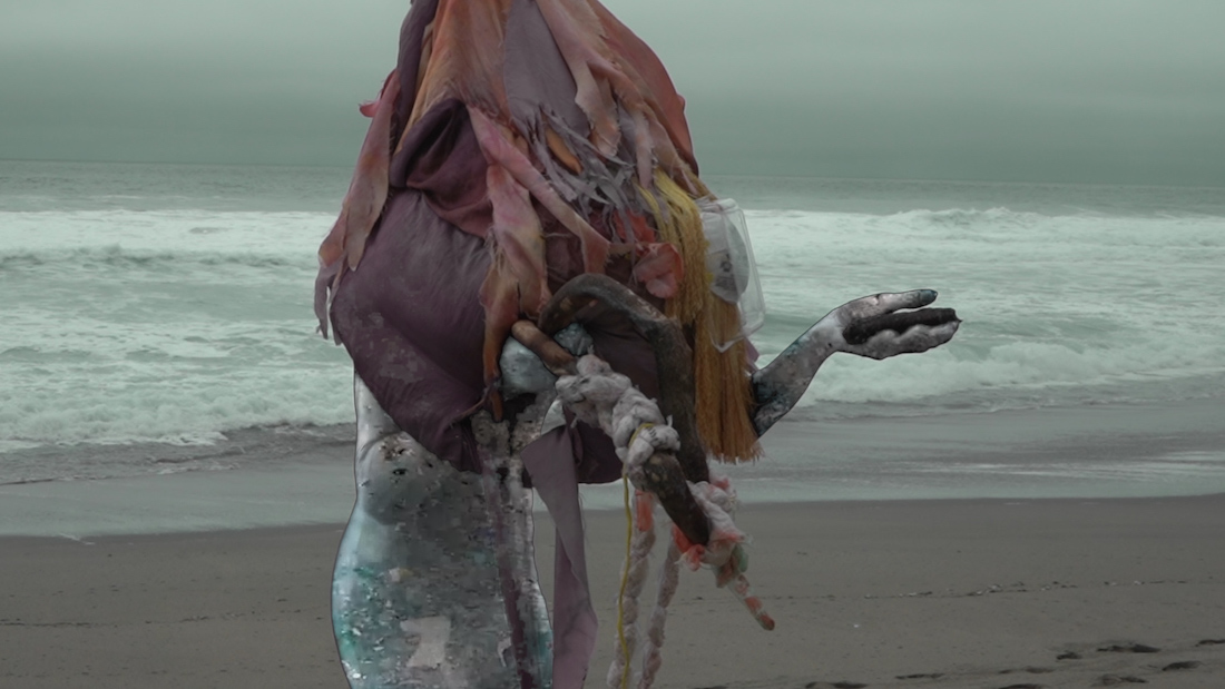 A figure on the beach appears to be tangled in plastic and trash from the waist up in a scene from Connie Zheng's video The Lonely Age (Part 1)