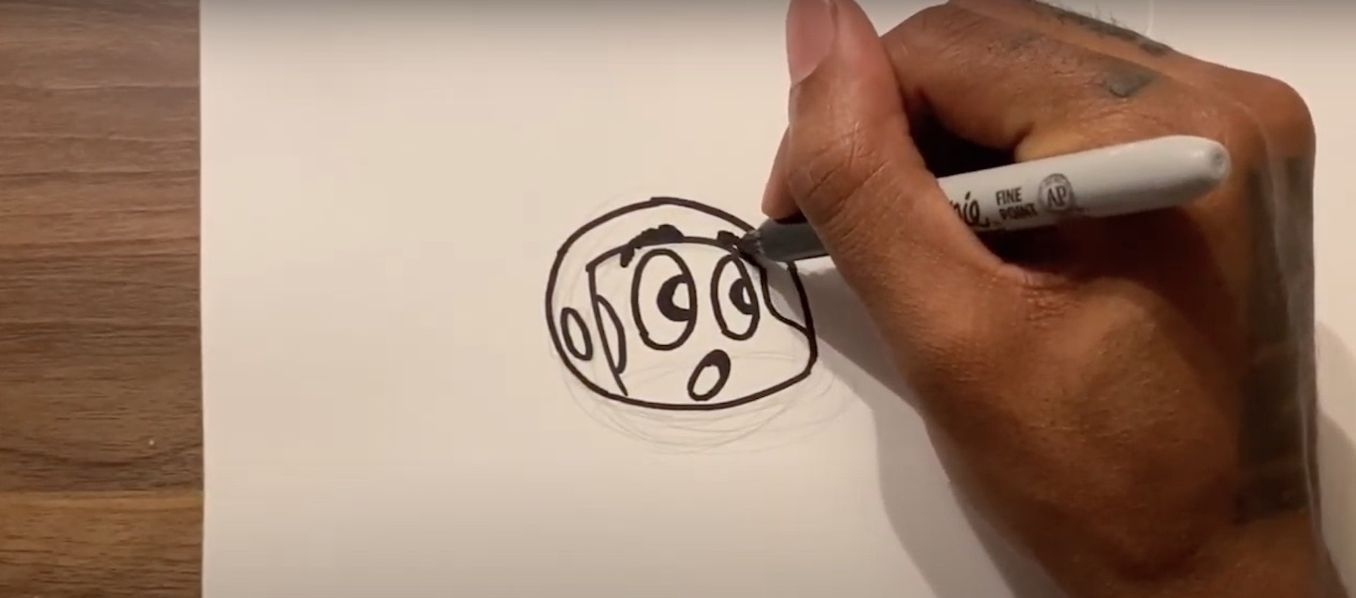 The hand of artist Hakim Callwood draws the head of his cartoon character Spaceboy