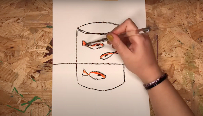 Art educator Courtney Hall's hand is seen watercoloring a drawing inspired by the Henri Matisse painting The Goldfish