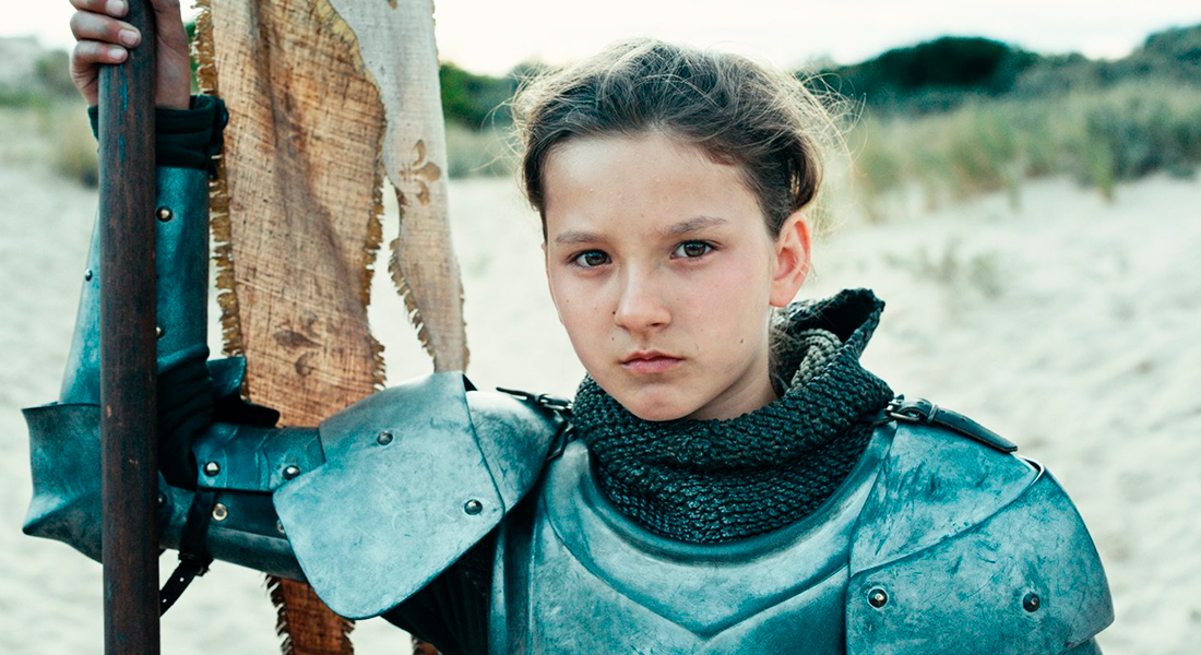 Lisa Leplat Prudhomme as Joan of Arc in knight's armor holding a flag pole on her with her right hand