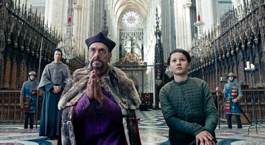 Lisa Leplat Prudhomme as Joan of Arc with a man kneeling in a cathedral with guards behind them