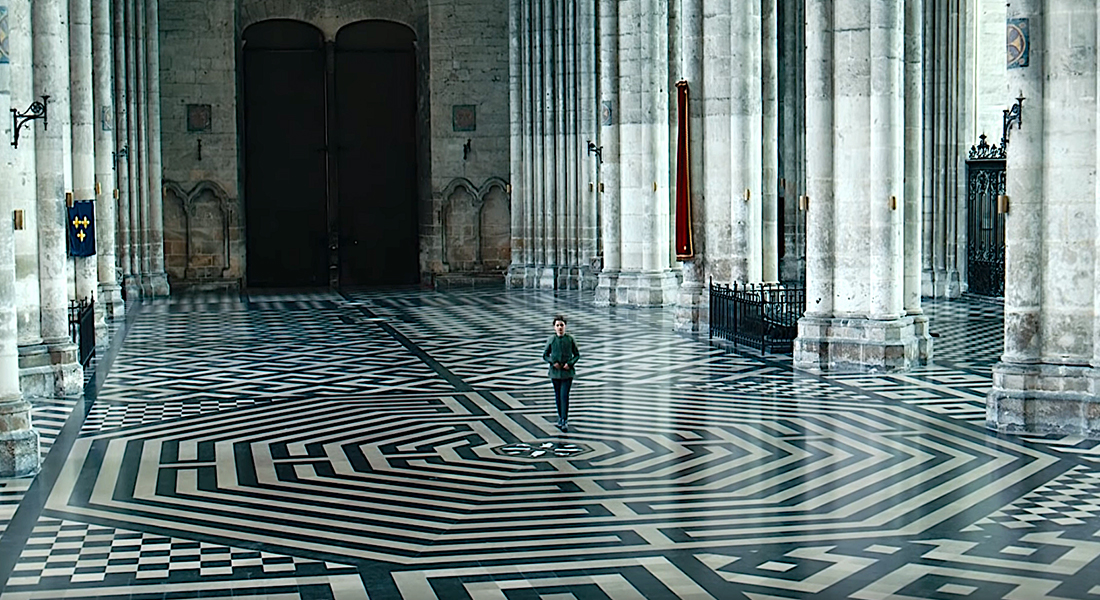 a girl walking in a great hall with patterned floors