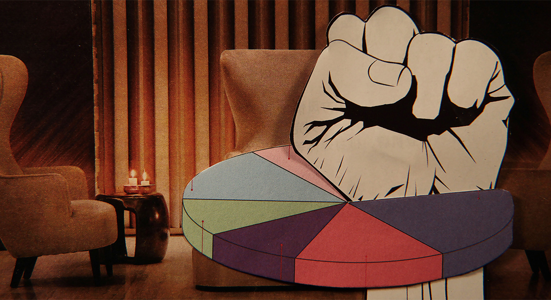In this color collage, a still from the film, a paper fist punches through a pie chart with a vintage lounge setting as the background.