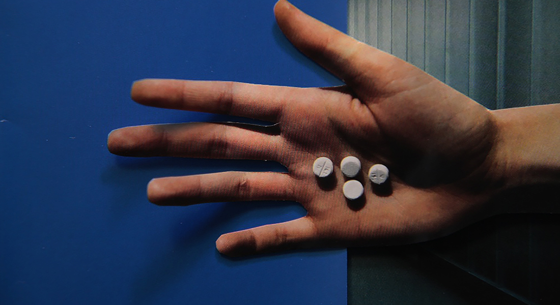 In this color collage, a still from the film, a hand holds four white pills in its palm against a blue background.