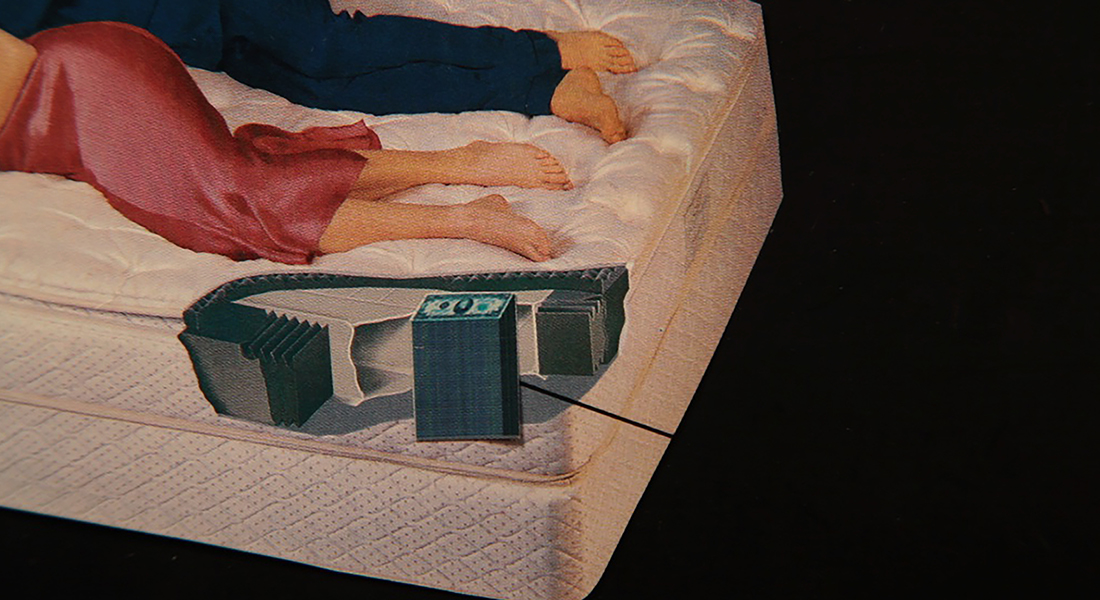 In this color collage, a still from the film, a bottom half of a mattress sits on a black background. A couple lounge on the bed. We see their feet and a cut through of the mattress revealing a stash of money.