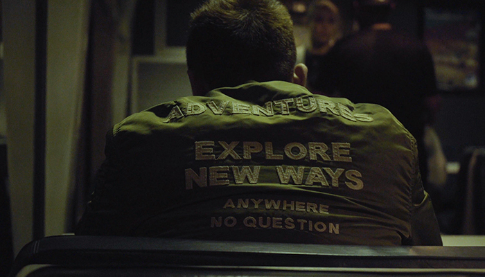 A seated man wearing a jacket with the words 'adventures explore new ways anywhere no questions'