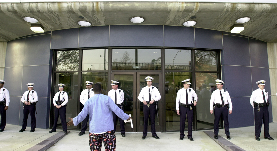 A black man stands in front of a line of Cincinnati police officers.