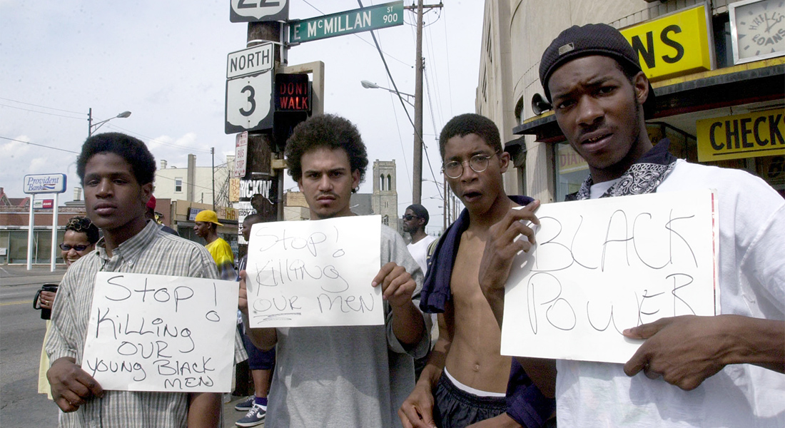 Four black men hold signs protesting the killing of young black men.