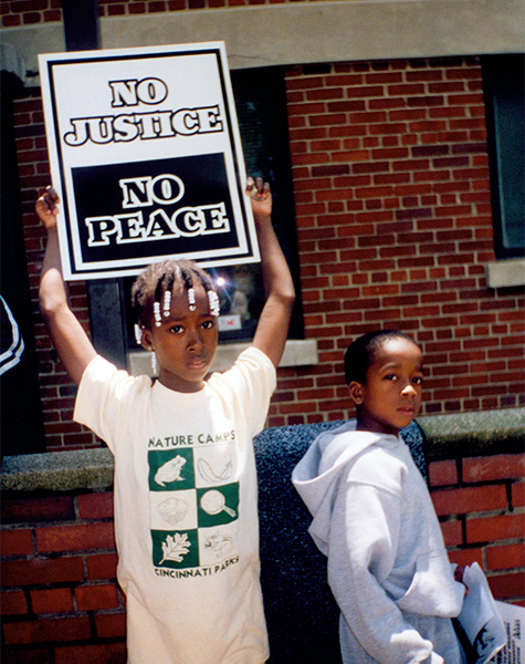 "Two black children look at the camera while one holds a sign that says ""No Justice, No Peace""."