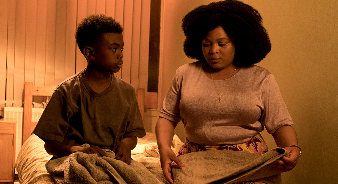 A young Femi talks to his birth mother Yinka (Gbemisola Ikumelo) in his bedroom