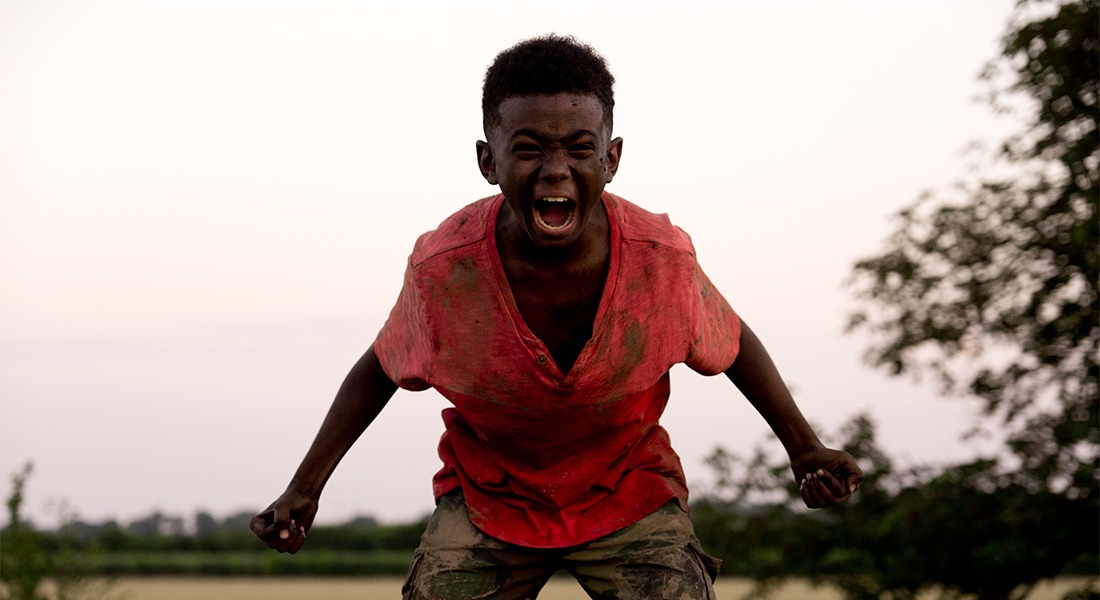 A muddied young Femi screams in rage at the camera