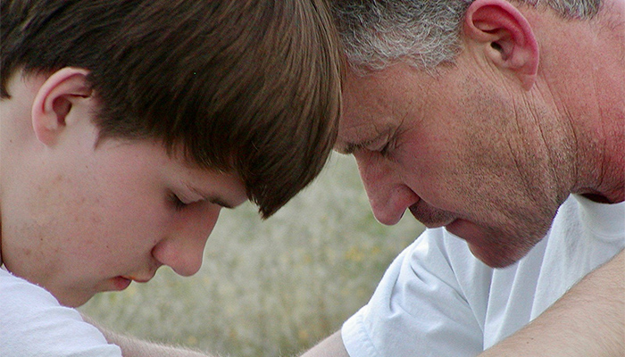 A father and child, Ryan and Rob Robertson, pray together touching foreheads.