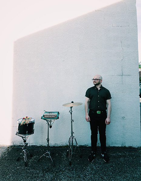 Noah Demland poses with a tom, hi-hat cymbal, and typewriter outdoors against a white wall