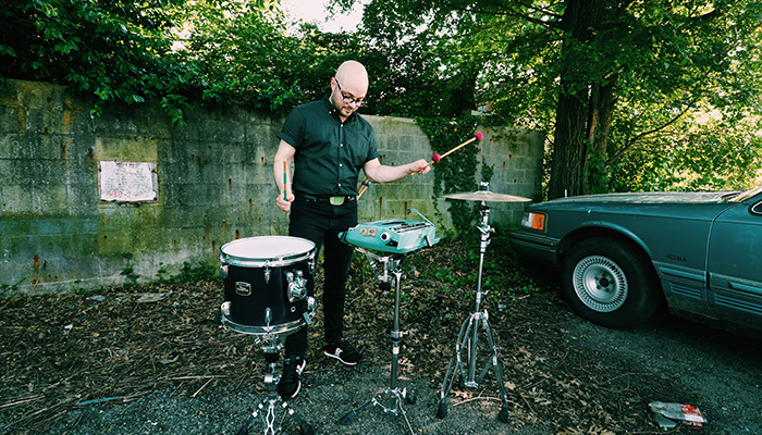 Noah Demland uses mallets to play a tom, hi-hat cymbal, and typewriter outdoors in front of cinder block and vines