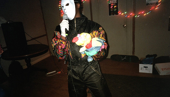 A person in a mask and jumpsuit holds a microphone in one hand and a puppet in the other.