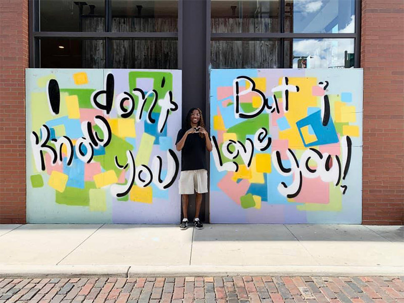 "Columbus artist Hakim Callwood stands in front of a mural he's created for a boarded up storefront that reads, ""I don't know you but I love you"""