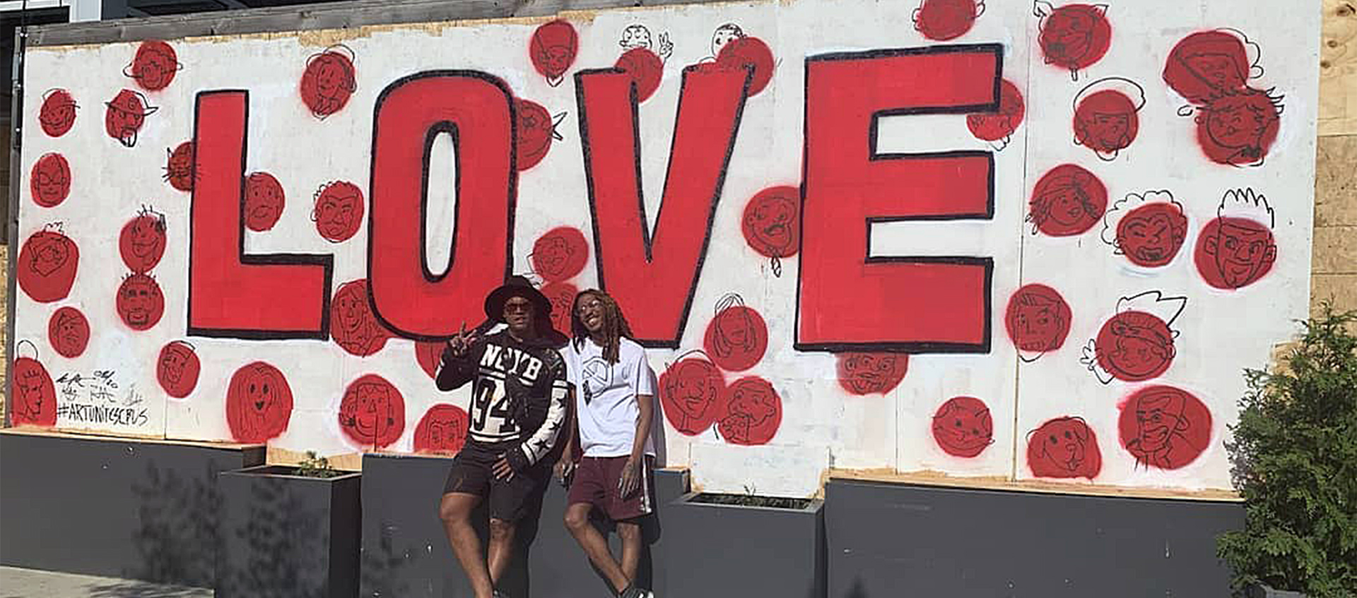 "Columbus artists Bryan Moss and Hakim Callwood stand in front of a ""Love"" mural on the front of Donato's in the Short North"