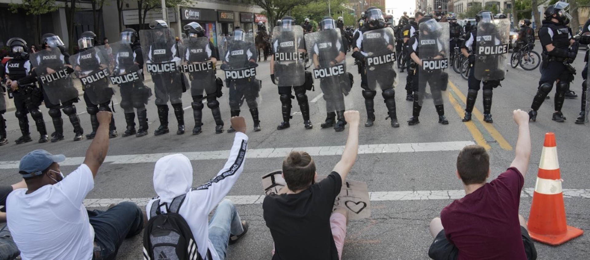 A line of four individuals protesting the death of George Floyd seated on the street, each with one fist raised, facing a line of police in riot gear