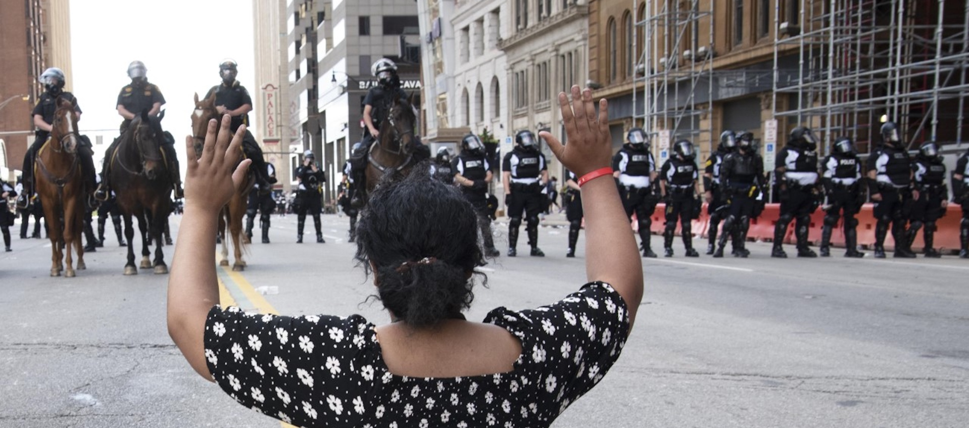 A young woman of color with her back to the camera sits with her arms raised in front of a line of police officers during a protest for the death of George Floyd in Columbus, Ohio, Saturday, May 30, 2020; photo: Mary Barczak