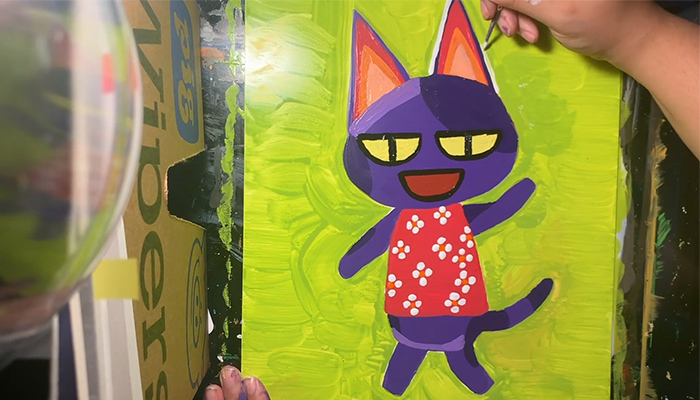 The hand of artist Bethani Blake paints a colorful portrait of Bob the Cat from the videogame Animal Crossing