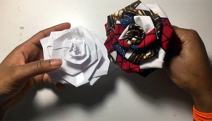 The hands of Columbus artist Claudia Owusu hold rosebuds made of white paper and patterned fabric