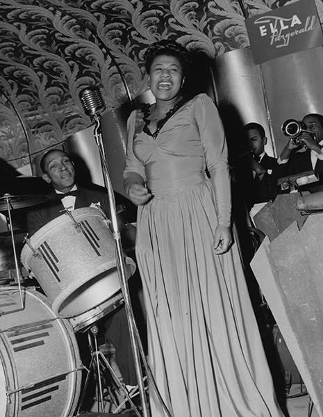 A black-and-white photo of Ella singing on stage in front of a drum kit