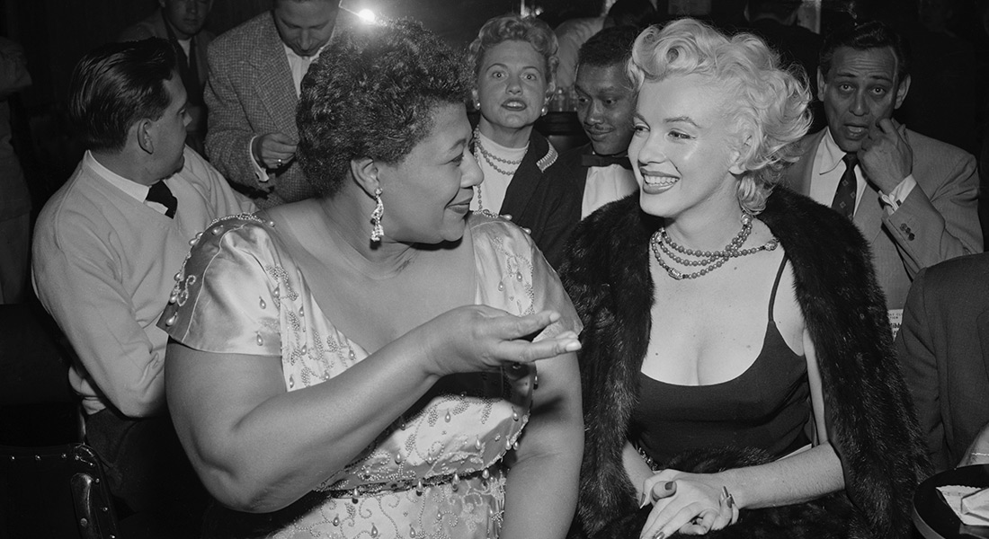A black-and-white photo of Ella talking to Marilyn Monroe