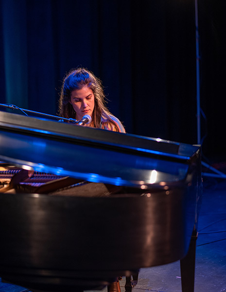 Erin Durant sits at a piano and sings into a microphone