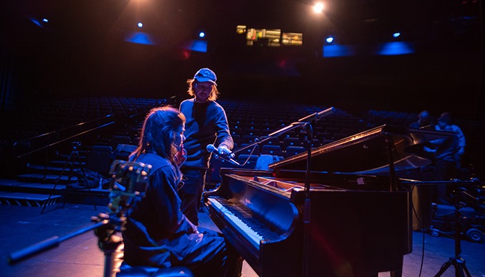 Erin Durant sits at a piano on stage as a crew person places a mic in front of her