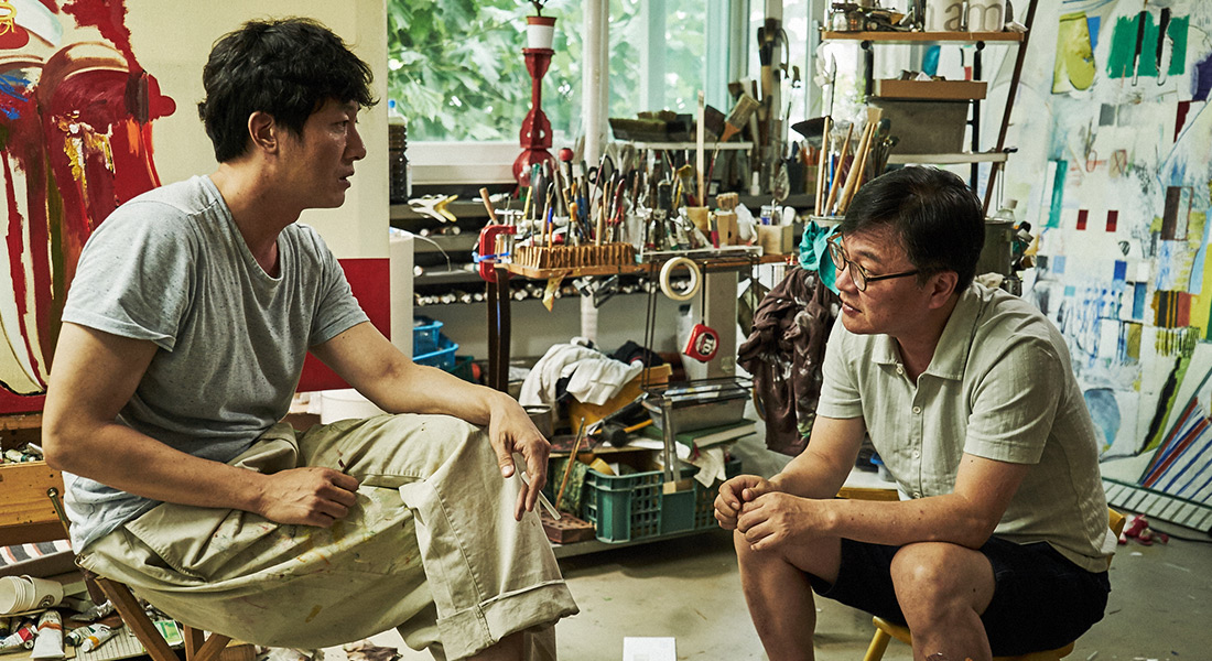Two men converse in a painter's studio