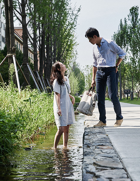 A woman standing in a stream looks up at a man on a sidewalk