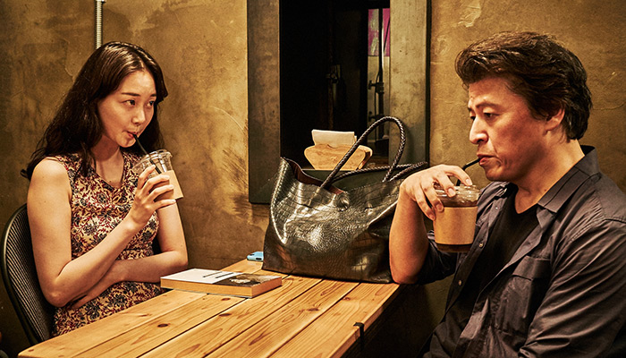 Couple Minjung and Youngsoo sip coffees across a wooden table