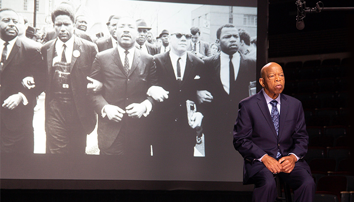 Rep. John Lewis stands in front of a projection of a historic black-and-white photo