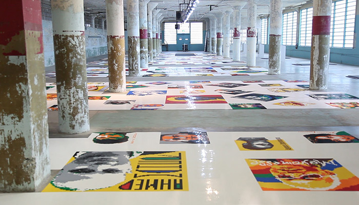 An installation view of Ai Weiwei's Trace, consisting of 190 portraits of dissidents made of Lego bricks arrayed flat on the floor of the former Alcatraz penitentiary