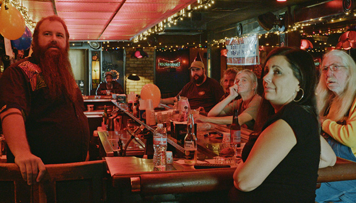 A group of six men and women of various ages sit a dive bar counter tended by a bearded man