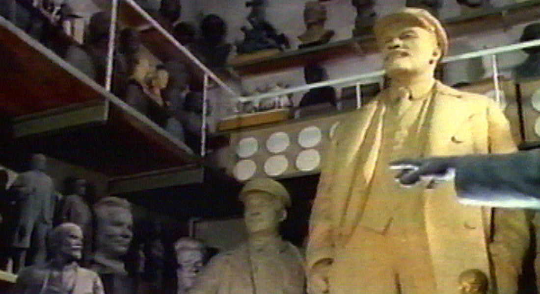 A warehouse full of old Soviet monuments, with a statue of Lenin at right