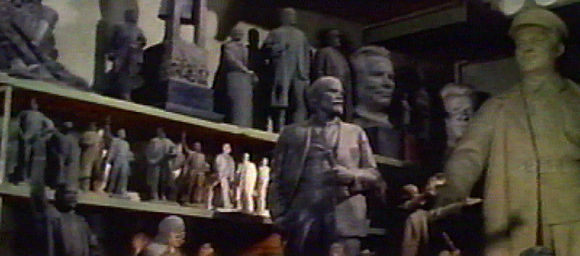 A warehouse full of old Soviet monuments, with a statue of Lenin at the center of the shot