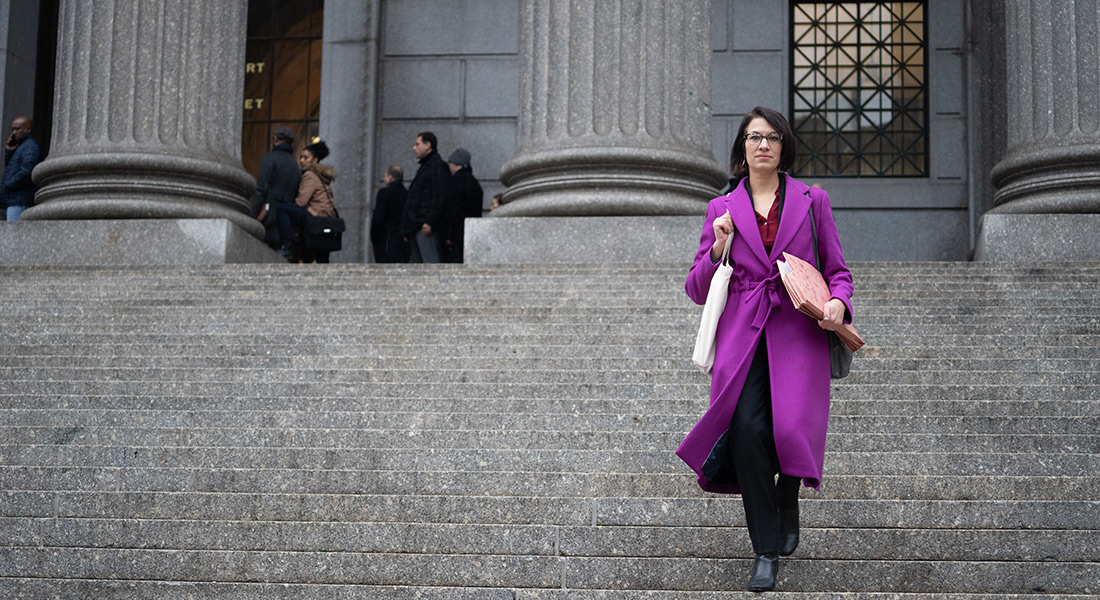 ACLU lawyer Brigitte Amiri descends a court staircase with files in hand wearing a purple coat